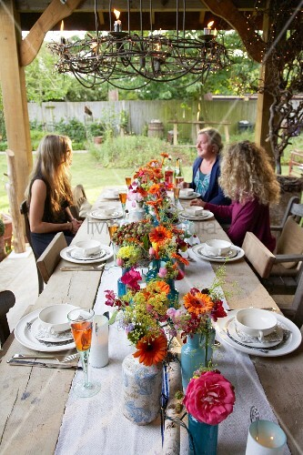 Rustic wooden table decorated with autumn flowers on roofed terrace: three women in background