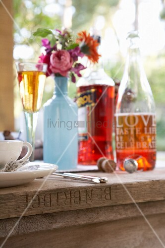 Bottle painted pale blue and used as vase for autumn flowers and drinks on rustic wooden table