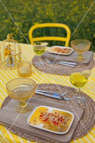 Orange desert for two on yellow and white striped tablecloth and rustic place mats