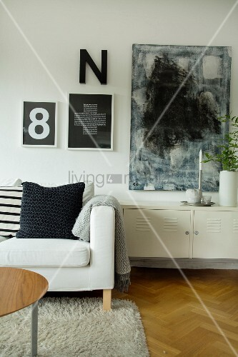 Scatter cushions on sofa next to low metal locker below black and white abstract artworks and typographical art on wall