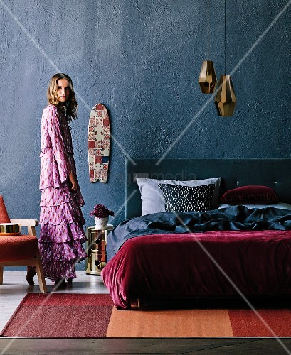 Schlafraum mit Doppelbett vor grauer Wand unter Messing Pendelleuchten, Frau mit Bohemian-Flair