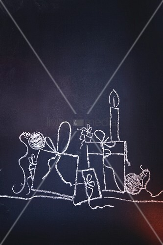 Gifts, candles and Christmas baubles drawn on chalk on a blackboard