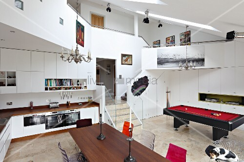 View across dining table and through fitted kitchen to pool table in open-plan interior with encircling gallery