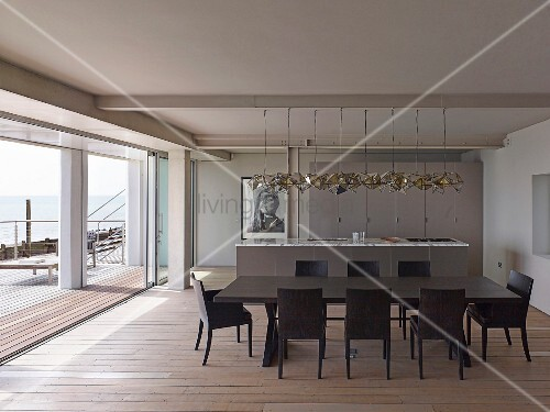 Dark dining table and matching chairs on wooden floor; kitchen counter and designer pendant lamps in open-plan interior with view of sea across terrace