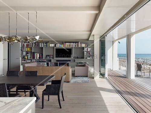Open-plan interior with dining area, lounge area and open folding glass doors with view of sea