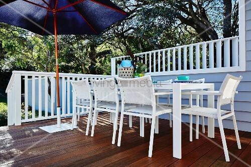 weisse outdoor st hle und tisch auf terrasse seitlich blauer sonnenschirm vor weisser. Black Bedroom Furniture Sets. Home Design Ideas
