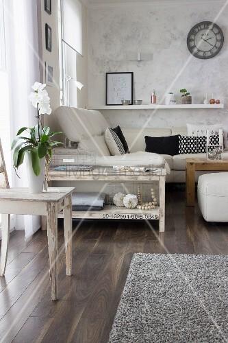 weiße Orchidee auf Holzstuhl vor schmalem, selbstgebautem Konsolentisch neben Sofa