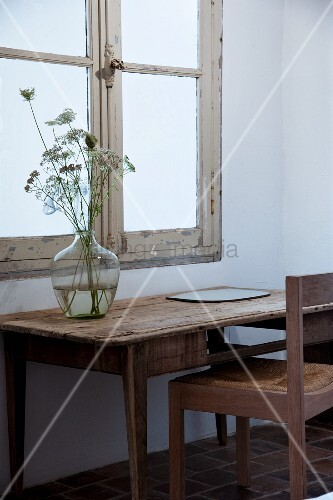 Demijohn on rustic table and wooden chair below vintage window