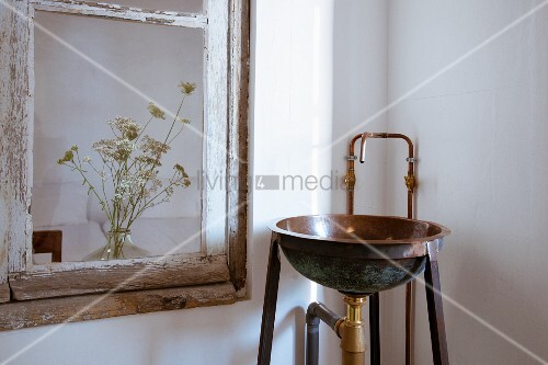 Metal washbasin and tap fitting next to vintage window