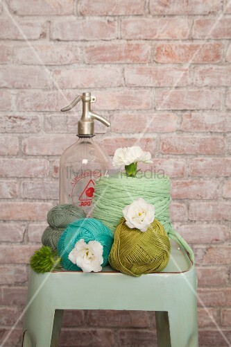 Crochet yarn in shades of green and blue with white flowers and vintage soda siphon on vintage stool against brick wall