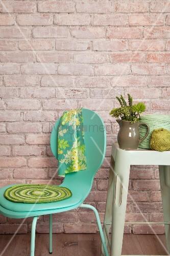 Gehäkelte Sitzauflage auf türkisem Stuhl neben Garnknäuel und Keramikkrug auf Vintage Hocker