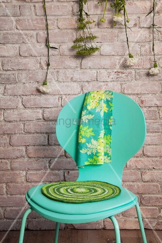 Gehäkelte, runde Sitzauflage in Grüntönen auf türkisgrünem Stuhl vor Backsteinwand