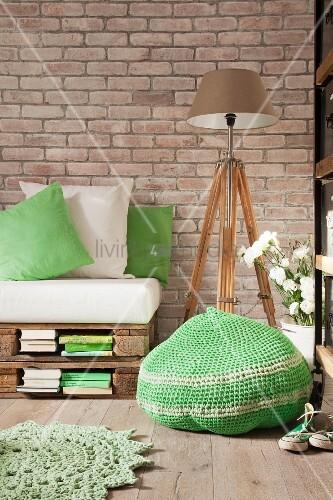 Gehäkelter Sitzpouf in Grün, dahinter Palettensofa und Leuchte auf Holzstativ in Vintage Ambiente