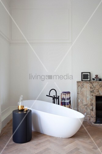 Freistehende weiße Badewanne und zylindrischer, schwarzer Beistelltisch auf Fischgrätparkett in minimalistischem Badezimmer