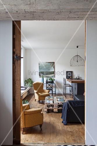 Blick Auf Armlehnsessel Um Paletten Couchtisch In Wohnzimmer Mit  Küchentheke Im Hintergrund
