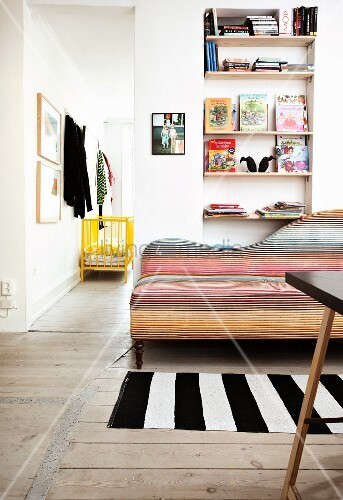 Sofa with curved backrest and colourful upholstery in narrow stripes next to open doorway with view of yellow-painted cot
