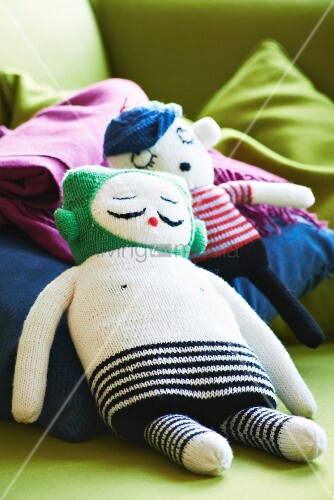 Two knitted dolls on blue cushion