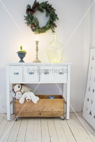 Kranz über weißer Schubladenkommode, Holzkiste mit Spielzeug