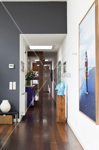 Grey-painted wall and dark wooden floor in foyer with artwork on wooden plinth and painting on white wall