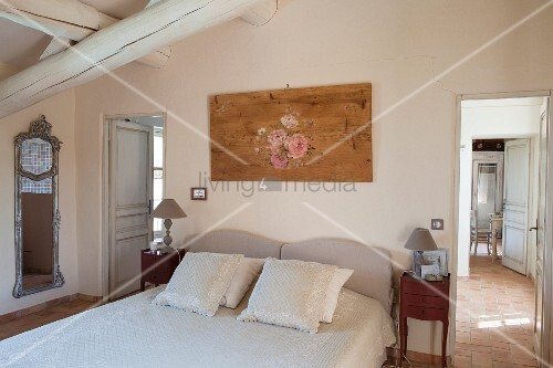 Scatter cushions arranged on double bed below wood-beamed ceiling; open door with view into adjoining room to one side