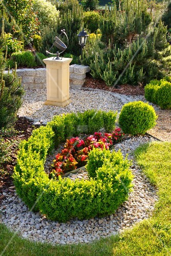 Landscaped garden with bed of red begonias, box hedges and artwork on plinth