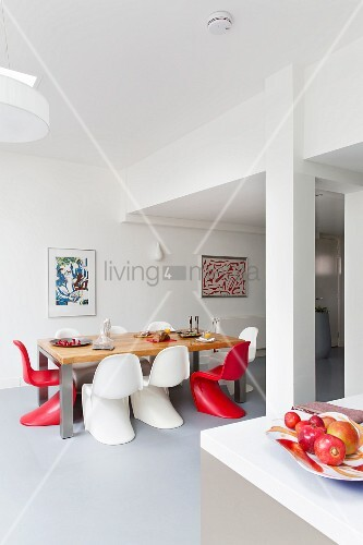 Red and white classic chairs around table in dining area in bright, open-plan interior