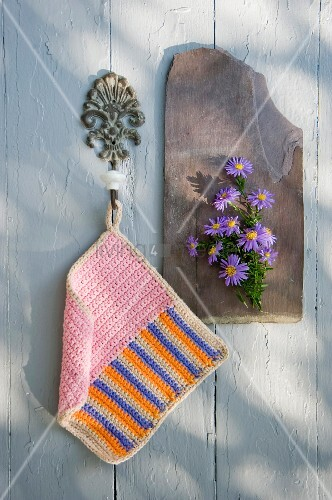 Hand-crocheted pot holder with graphic pattern hanging from vintage hook