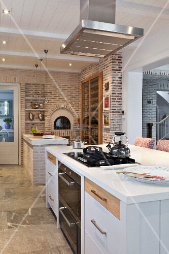 Modern, open-plan kitchen with exposed brick wall, masonry pizza oven and fitted, glass-fronted cabinet