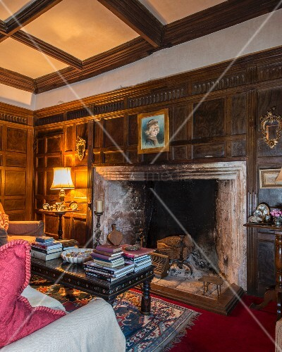 Wood panelling, coffered ceiling and books stacked on coffee table in front of large fireplace in classic interior
