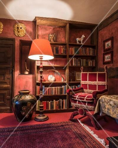 Herrschaftliche antike Bibliotheksecke, leuchtende Stehlampe neben antikem Lesesessel mit Samtbezug vor Bücherregal
