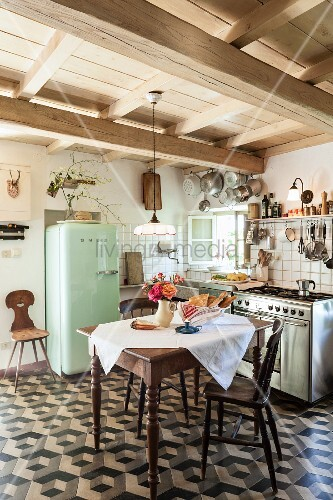 White tablecloth on table and wooden chairs on geometric tiled floor in Mediterranean kitchen