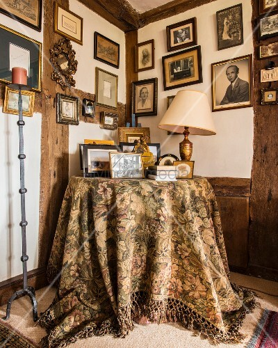 Framed family photos on walls above round table with tapestry tablecloth