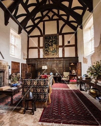 Large, elegant, great hall with exposed and restored roof structure and tapestry-covered sofa in foreground