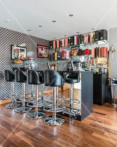 Bar stools with black leather seats in front of mirrored counter in open-plan home bar