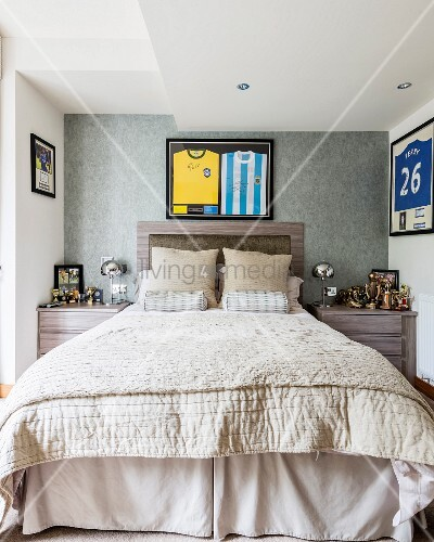 Double bed with headboard below framed sports strips flanked by collection of trophies on bedside tables in elegant bedroom