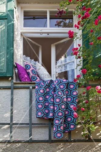 Selbstgehäkelte Tagesdecke und Kissenbezüge in 'Granny Square' auf Fensterbrett von traditionellem Sprossenfenster