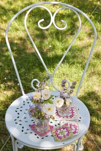 Blumensträußchen mit gehäkelten Untersetzern auf weißem Metallstuhl im Garten
