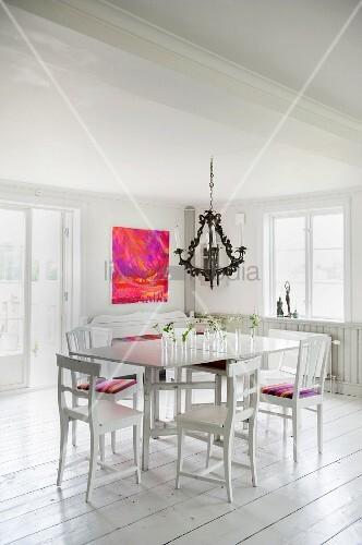 Weisser Tisch mit Holzstühlen unter Kronleuchter in ländlichem Ambiente mit weißem Dielenboden und modernem Bild