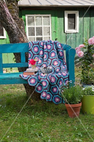 Häkeldecke aus Hexagons in Blau- und Violetttönen auf Gartenbank vor Hütte