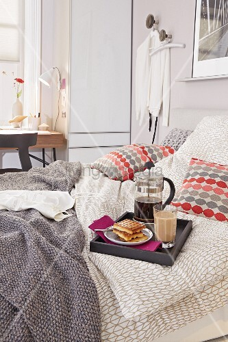 A breakfast tray with coffee and pastries on a double bed