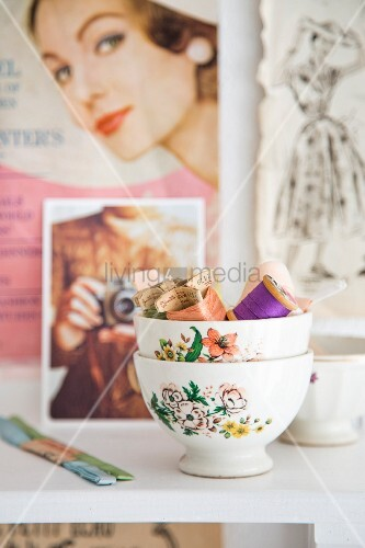 Stacked vintage bowls of colourful sewing utensils in front of clippings from retro fashion magazines