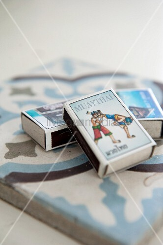 Three matchboxes with pictures on tops arranged on ornamental tile
