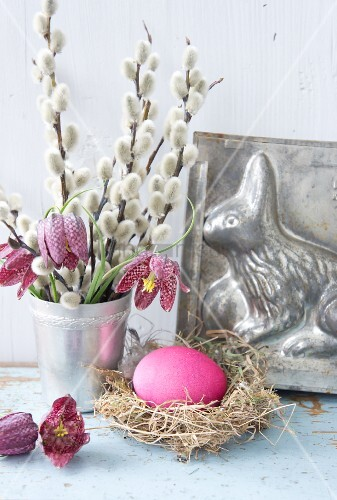 Easter still-life arrangement with willow catkins, Easter nest, snake's head fritillaries and Easter bunny cake tin