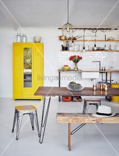 Classic stools and wooden table in simple dining area in front of yellow cupboard and kitchen counter