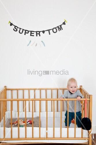 Kleinkind im Gitterbett stehend, an Wand Jungenname aus schwarzen Buchstaben aufgehängt