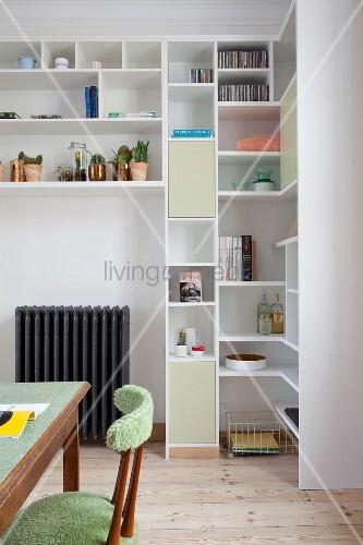 Massgefertigtes weißes Regal mit geschlossenen und offenen Modulen, im Vordergrund gepolsterter Retro Holzstuhl