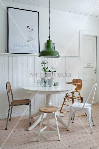 Runder Tisch mit verschiedenen Stühlen vor Wand mit Bretterverkleidung