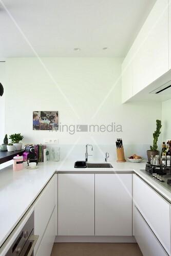 U-förmige Küche mit Oberschränken und weißer Küchenarbeitsplatte ...
