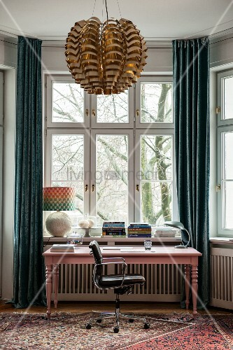 Pink-painted desk in window bay between floor-length curtains and pendant lamp with metallic lampshade in foreground