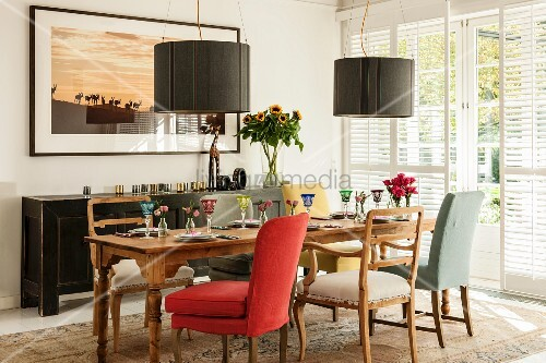 Various upholstered chairs around set wooden table below modern pendant lamps with charcoal-grey lampshades